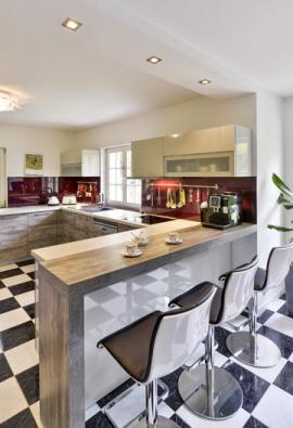 Obložení stěn zakuchyňskou sestavou vyřešila designérka tvrzeným sklem vefialovém odstínu, velmi dobře se udržuje apříjemně odráží světlo.