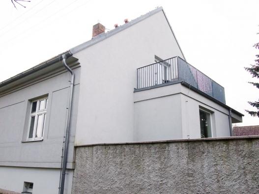 Pavlíkov - fasáda citlivě zrekonstruovaného domu je jemně šedá, což pěkně koresponduje s pozinkovanými klempířskými prvky a jednoduchým zábradlím na balkónku nad vchodovou verandou.