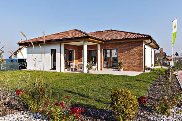 Nenápadný nízký dům svalbovou střechou se propojuje se zahradou přes rohovou terasu, kterou zútulňuje cihelný obklad. Dá se tu relaxovat nasluníčku iposedět vpříjemném stínu ujídelního stolu.