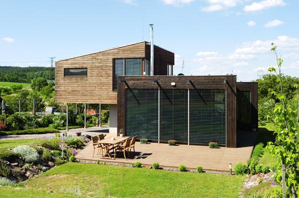 Při pohledu ze zahrady by málokdo uvěřil, že dům vyrůstal na etapy – nejdříve zděné přízemí a pak dřevěné patro. Obojí sjednocuje modřínový obklad fasády. Přes dřevěnou palubu terasy se jde ze zahrady do prosklené společné obývací části.