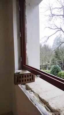 Pro dočasné zafixování okna v horní poloze posloužily dvě cihly a kousky sádrokartonu.