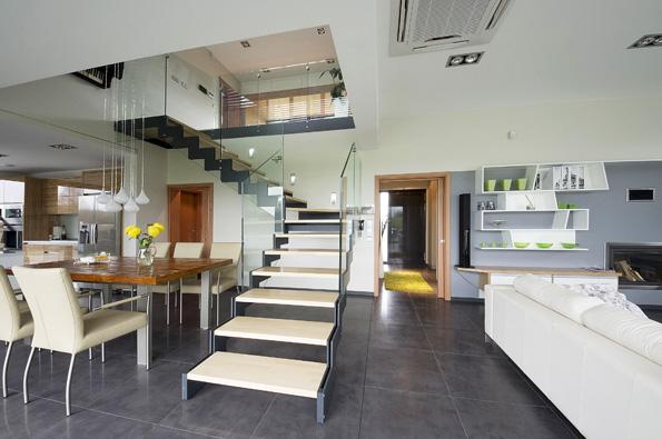 Interiérové schodiště vnejoblíbenější materiálové kombinaci  kovu, dřeva askla. Sklo zde slouží ijako zábradlí horní podesty (galerie).