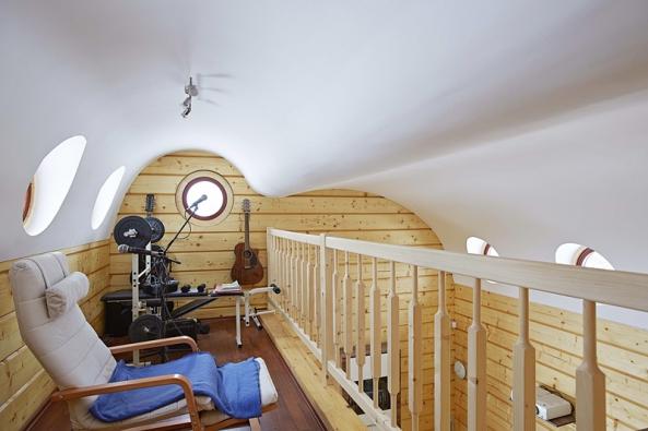 Mistrovsky zvládnutá zvlněná sádrokartonová konstrukce nad obytným prostorem moderní nízkoenergetické dřevostavby připomínající interiér kajuty (RIGIPS).
