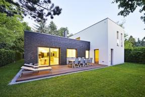 Architektonickou kompozici domu tvoří dvě navzájem kolmé hmoty tvaru kvádru.  Jednopodlažní část, zvýrazněná páskovým obkladem Roeben, obsahuje obývací pokoj aje ze dvou podélných stran lemována terasami.
