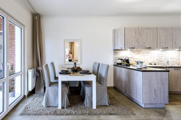 Dlažba vimitaci kamene stylově ladí skorpusy kuchyňské linky sdekorem dřeva aopticky navazuje také naobklad zdi (1).