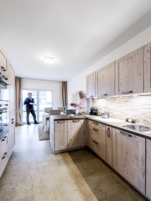 Dlažba vimitaci kamene stylově ladí skorpusy kuchyňské linky sdekorem dřeva aopticky navazuje také naobklad zdi (2).