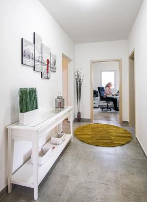 Zpředsíně se vstupuje dochodby oddělující hlavní obytnou část oddruhé poloviny domu, vekteré se nachází dvě koupelny, ložnice apracovny.