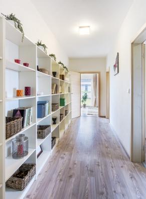"""Dlouhou chodbu zdobí otevřené úložné prostory, které lze využít prakticky – naukládání knih, ale také """"pouze"""" kvystavení květin adalších drobných dekorací."""