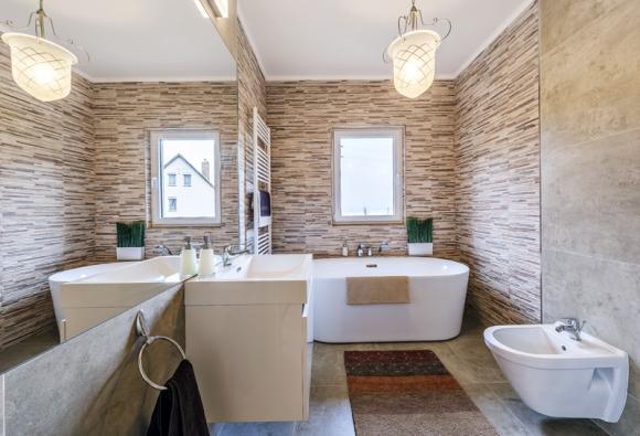 Okno přivádí do koupelny denní světlo  a umožňuje dobře ji vyvětrat. Obklady adlažba jsou ze stejné série jako vkuchyni apotvrzují tak jednotný vizuální koncept celého domu.