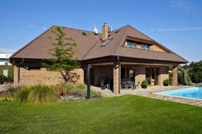Dům je rozdělen nadva trakty – garáž  aspolečnou obývací část. Dominantní valbová střecha svelkým přesahem arežné zdivo charakterizují rukopis architekta Jiřího Houši.