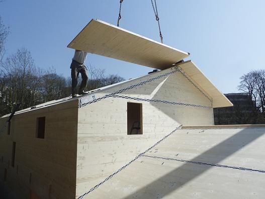 """Některé typy dřevostaveb představují v továrně dokonale zpracované stavebnice, které se na místě """"jen"""" skládají. Na snímku je zachyceno ukládání střešních elementů (NOVATOP)."""