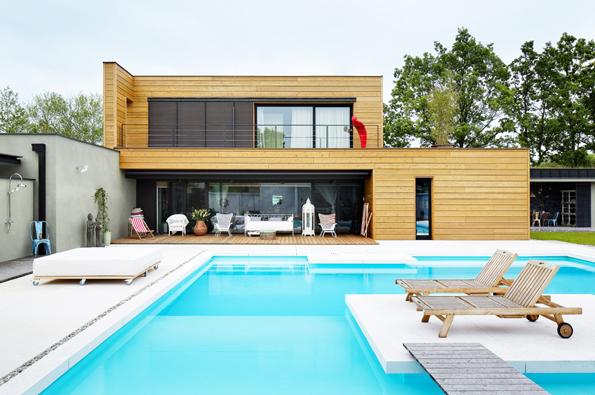 Zletadla připomíná dům navržený doL hokejku. Tvar umožnil vytvoření atria sbazénem. Architekti použili nafasádu kombinaci omítky aobkladu zcedrového dřeva. Velkoformátová okna mají subtilní hliníkové rámy.