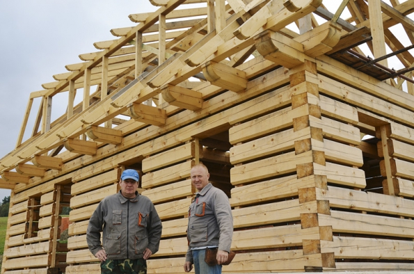 Dvojice tesařských mistrů, pánové Prokůpek a Matura před skoro dokončenou hrubou stavbou roubenky v Jílovém.