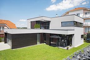 Dvojpodlažní hmota domu brání nechtěným pohledům ze sousedního bytového domu, gabionová zeď sgaráží vymezují privátní zahradu.
