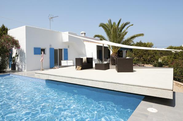 Sněhobílé omítky, blankytné nebe amodré okenice jsou pro španělské Středomoří typické. Vyvýšená betonová deska nad bazénem tvoří terasu azároveň zastřešuje technické zázemí domu, které se pod ní ukrývá, zapuštěné vesvahu.