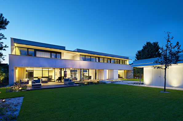 Moderní architektonicky zajímavá dvoupodlažní budova se zapuštěným suterénem upoutá naprvní pohled vstupní fasádou, prosklenými plochami, velkým balkonem ipřesahem střechy.