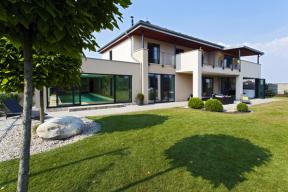Vnější a vnitřní prostor se svobodně prolíná. Upravená zahrada s tenisovým kurtem vstupuje velkoformátovými dveřmi do dvoupodlažní obytné hmoty domu, na niž navazuje přízemní bazén.