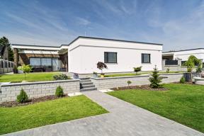 Jednoduchou kompozici domu zvýrazňuje kombinace hladkých ploch aplastického obkladu ze štípaného kamene.
