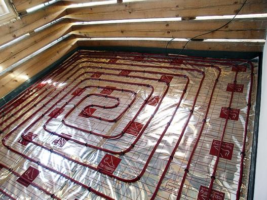 Na podlahový polystyren je položena reflexní fólie s topnými hadicemi fixovanými svorkami.