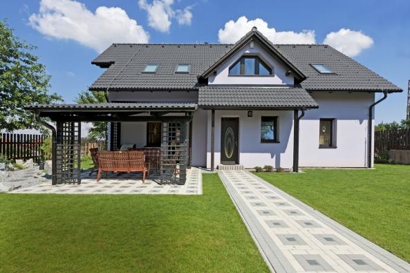 Symetricky uspořádané vstupní průčelí se sedlovou taškovou střechou aarkýřem dodává domu nádech tradice asolidnosti.