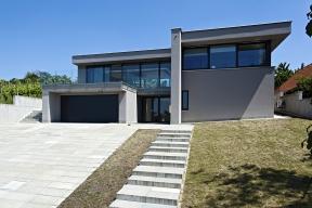 """Původní část domu reprezentuje jeho nynější pravá polovina spásovým oknem vpatře, zachovala se také garáž. Střešní terasa a prosklená """"nástavba"""" jsou zcela nové, stejně jako nástupní schodiště apříjezdová plocha zbetonových prefabrikátů aveškeré další exteriérové úpravy."""