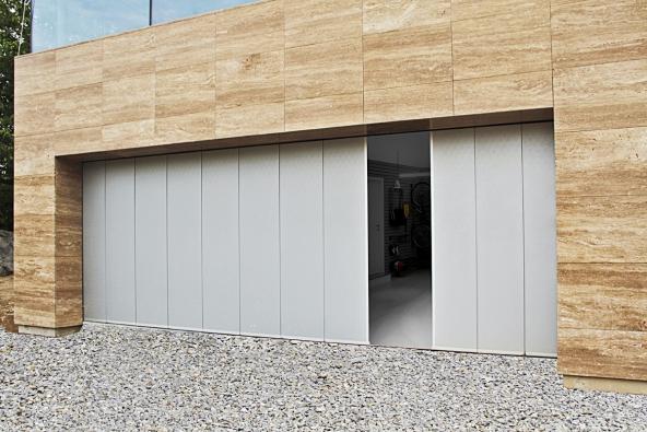 Jednou z výhod garážových vrat otevírajících se do boku je možnost jednoduchým pootevřením získat provozní průchod (LOMAX)