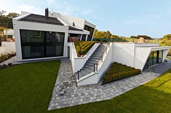 Společná obývací část domu pokračuje venku velkou terasou, pod níž je zakomponována malá vestavba – letní relaxační prostor.
