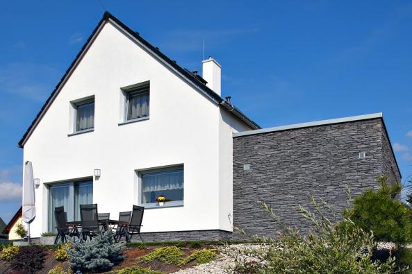Vupravené variantě má dům Ája vhlavním průčelí francouzské okno naterasu  azvýchodní strany je přistavěno garážové stání obložené štípanou břidlicí.