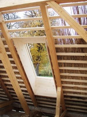 Detail střešního okna při rekonstrukci střechy na statku v Chomoutově Lhotě, kde byly bobrovky nahrazeny rákosovými doškami. Pro došky platí, že čím je střecha strmější, tím má krytina delší životnost (RAKOSOVESTRECHY.CZ)