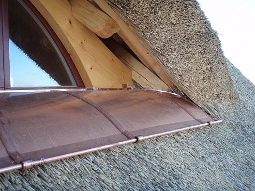 Kombinace rákosových došků a klempířských prvků z měděného plechu na střeše nově postaveného rodinného domu Pazderna.