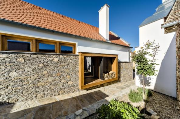 Atraktivním poslem moderní doby vautenticky zrekonstruované stavbě je výrazné atypické okno svýhledem nadvorek azeleň.