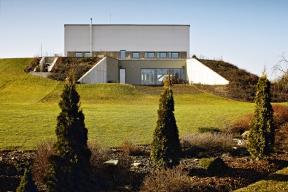 Ze strany severovýchodní se dům jeví jako bílý hranol snízkým pásem oken nad zeleným svahem se zapuštěnou terasou.