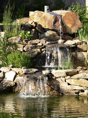 Volně padající voda, šplouchající mezi kameny. Pracnější, ale přirozenější řešení.