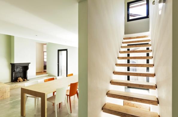 Schodiště sevřené mezi dvěma stěnami tvořené pouze stupnicemi osazenými natrny je efektivním azároveň jednoduchým řešením. Ivtomto případě zvítězil minimalismus, před kolaudací je potřeba umístit alespoň najednu stranu madlo.