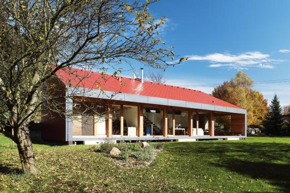 Plně prosklená jižní fasáda je orámována šedým cembonitovým obkladem, který krásně kontrastuje sčervenými střešními šablonami. Dům má jednoduchý, ale výrazný výtvarný koncept.