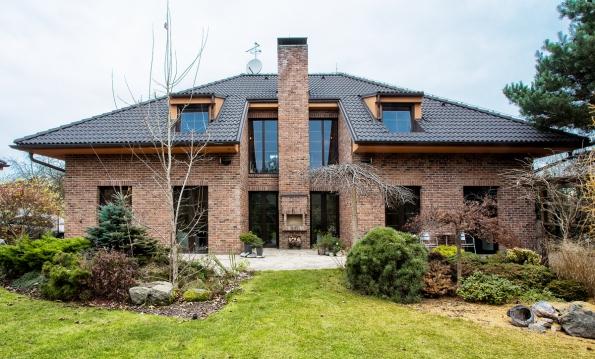 Prezentovaný příklad postmoderního domu využívá kombinace pálených lícových cihel nafasádě sodlišnou šedou betonovou střechou. Ta vytváří výrazně kontrastující prvek alze říci, že pálená taška by vesvé přirozené barevnosti tohoto efektu nedosáhla (Bramac)