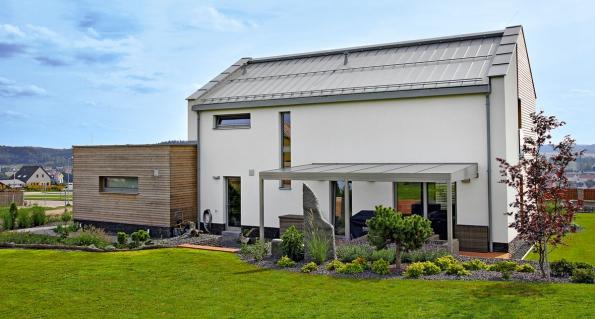 Moderní, ale relativně členitá stavba se třemi materiály fasády využívá plechové střechy jako jednotícího prvku. Sbarvou střechy jsou sladěné veškeré klempířské prvky ivýplně otvorů aocelové konstrukce. Lze říci, že sjinou krytinou by dům působil až příliš rozdrobeně, zde je výsledek vyvážený. Návrh Thermo Plus – projektový ateliér