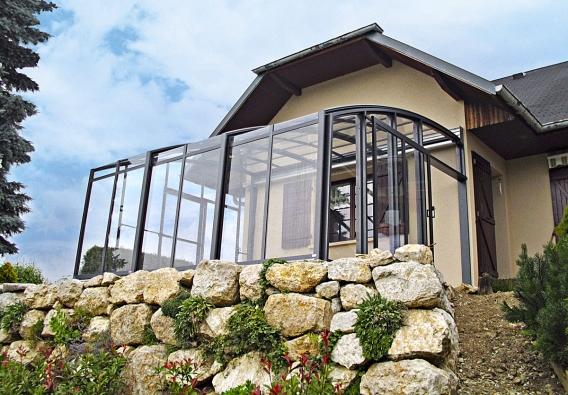 Posuvné, variabilní zastřešení terasy (výplň zpolykarbonátu nebo bezpečnostního skla) systémem Alukov zajišťuje pojezdový systém zkolejnic, osazených nastěně domu avpodlaze. Zimní zahrada se vlétě může zvětší části proměnit vterasu pod širým nebem.