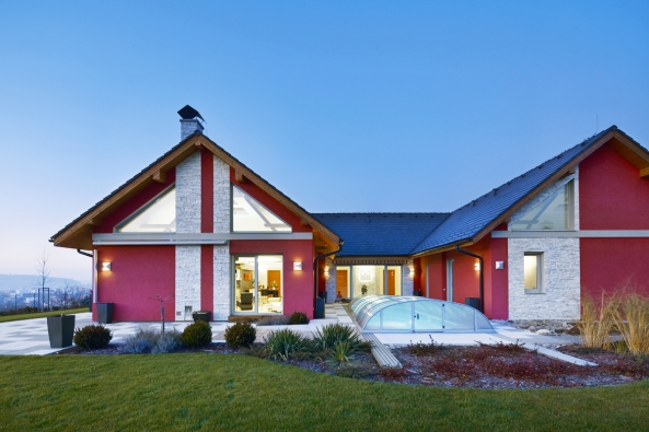 """Architekti zvolili tradiční venkovský tvar domu sšikmou střechou, použili moderní řešení amateriály. Půdorys přízemní stavby do""""U"""", vatriu je umístěný venkovní bazén. Šedé plastové rámy oken ladí svýraznou barvou fasády, která je kombinací omítky aimitace kamenného obkladu. Přírodní iumělý kámen je výrazným prvkem zajímavě řešené zahrady."""