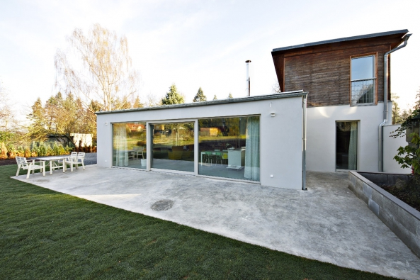 Nová přístavba nasedá napůvodní uzavřenější objekt aotevírá se západnímu slunci. Betonová terasa korespondující  snašedlou omítkou přízemního podlaží se vlévá dointeriéru vpodobě podlah zhladké betonové stěrky.