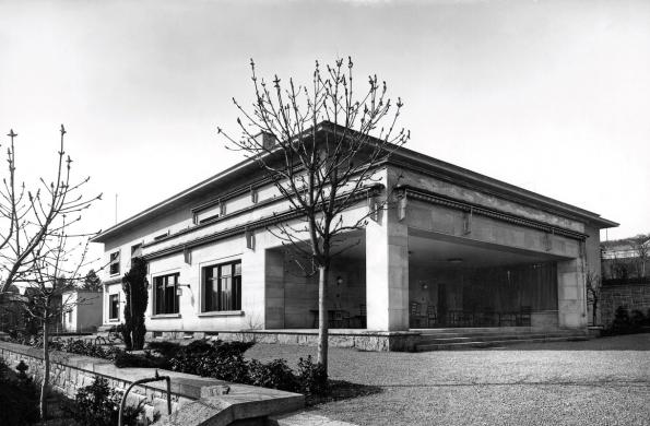 Jihovýchodní průčelí vily Stiassni spředsazenou zahradní lodžií avelkou terasou přístupnou zprivátních místností vpřízemí. Jižní avýchodní průčelí vily obepínají obytné terasy, které byly doplněny květinovými záhony. Fotograf: Rudolf de Sandalo. 30. léta 20. století.