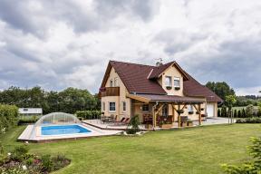 Zahrada s bazénem, terasou a zatravněnou plochou je koncipována jako logické vyústění a rozšíření obytného prostoru domu. Tomu napomáhá též zastřešení bazénu i terasy.