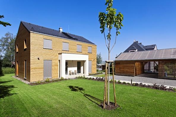 Sklon střechy architekti přizpůsobili sousední vile vhistorizujícím stylu, která pochází ze 30. let minulého století.  Uvstupu napozemek, mimo dům navrhli kryté dřevěné garážové stání zakomponované přímo douličního plotu.