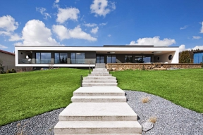 Přízemní stavba z monolitického železobetonu vznikla na principu dvou do sebe vložených objektů, jejichž odlišnost je přiznána různou barvou fasády.