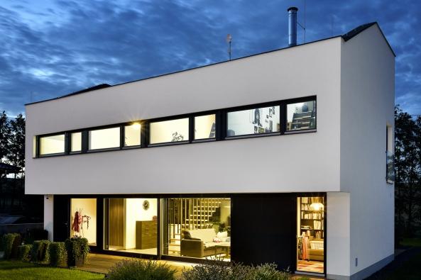 Dvoupodlažní stavbu sasymetrickou sedlovou střechou architekt umístil docentra pozemku. Široké horizontální okno zvýrazňuje přesahující horní podlaží, které stíní jižní prosklenou plochu.