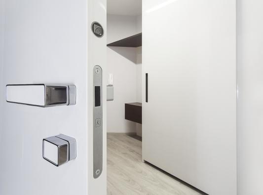 Detail dveří MILLENIUM spuncem originality HANÁK, klika se zámkem je sladěná sprovedením dveří. Vpozadí je šatní skříň HANÁK sposuvnými dveřmi.