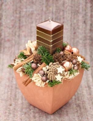 Do keramické nádoby je vložen svícen vpřírodních barvách, hranatou svíčku doplňují šišky, skořice, dřevěné hvězdičky, lýkové mašličky, bukvice akuličky ve dvou provedeních.