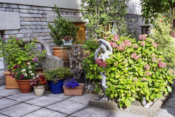 Nápadité artefakty a květiny v nádobách provázejí návštěvníka zahrady doslova na každém kroku. Zde se mění šedý venkovský dlážděný dvůr v pestrobarevný květinový kout.