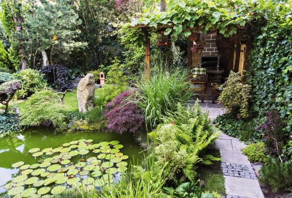 V zahradě jsou umístěny kromě jiného i zajímavě tvarované menhiry. Vše je viditelné z oken domu i od krbu s pergolou, kde se schází rodina a přátelé.