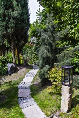 Vzrostlé výsadby vytvářejí přirozené předěly a romantická zákoutí plná překvapení. Tato cesta vede přes umělý pahorek a je doprovázena celou řadou rustikálních prvků.